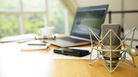 workspace for journalism with condenser microphone, laptop, cellphone and notepad on a desktop at the window, short panoramic banner for website headerwith blurred background, copy space