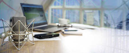 biznesowa przestrzeń robocza dla międzynarodowego dziennikarstwa z mikrofonem, laptopem, telefonem komórkowym i notatnikiem na biurku, panoramiczny baner z rozmytą matrycą w tle, kopia przestrzeń
