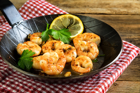 Fried tiger shrimps with garlic, lemon and italian parsley garnish in a black iron pan on a napkin and a rustic wooden table, selected focus Stock Photo