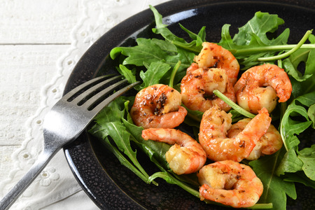 fried prawns or shrimps on arugula rocket salad with lemon and bread served on a black plate, white tablecloth, close up with selected focus, narrow depth of field
