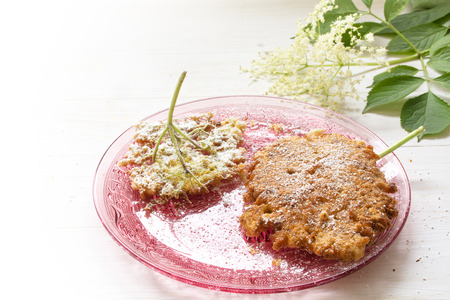 powdered: fried elderflower pancakes with icing sugar on a pink glass dish, gray wooden background fades to white, selected focus, narrow depth of field