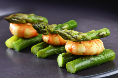 green asparagus with a tiger prawn, festive appetizer or buffet snack on a gray plate, close up, selected focus, narrow depth of field