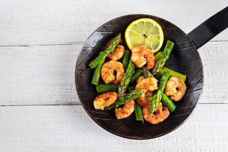 fried prawns or shrimps with  green asparagus peaks and a lemon slice in a black iron pan on rustic white painted wood with copy space, top view from above, selected focus