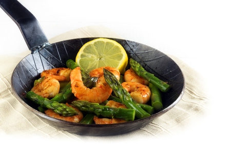 fried prawns or shrimps with  green asparagus peaks and a lemon slice in a black iron pan, corner background fades to white, copy space, selected focus, narrow depth of field