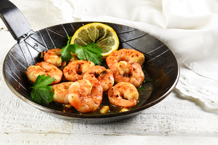 selected: prawns shrimps with garlic, lemon, spices and italian parsley garnish in a black pan on white painted rustic wood, selected focus, narrow depth of field Stock Photo