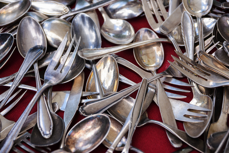 scattering: Old silver cutlery, hrown on a background of red fabric, selected focus, narrow depth of field Stock Photo