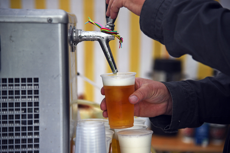 broaching: Mans hands at a beer tap pouring beer in plastic glasses in a marquee or tent at an open air festival event