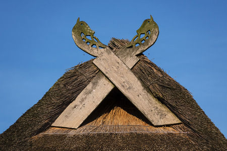 Wooden gabled boards in the form of horse heads on a thatched roof against a blue sky on a sunny day, typical of traditional houses in northern Germany Stock Photo