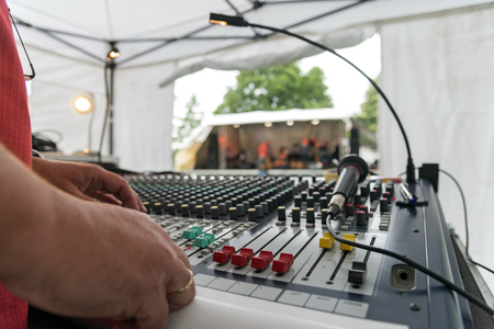 selected: Sound mixer at an open air music festival, view over the mixing panel with sliders and microphone, stage blurred in the background, selected focus, narrow depth of field