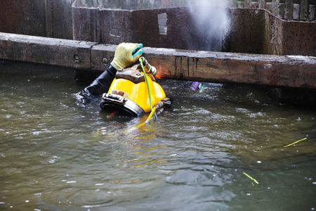 Diver with yellow helmet working in dirty water at the shore reinforcement in a canal, copy space