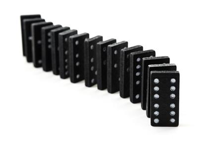 vecchi domino neri in una riga isolato su uno sfondo bianco . Messa a fuoco selettiva e ridotta profondità di campo