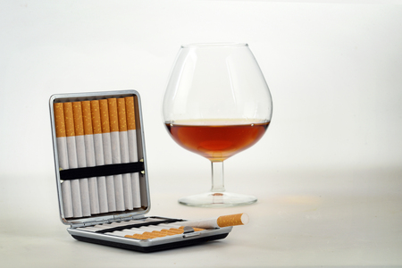 Tobacco and alcohol, cigarette case with filter cigarettes and a glass with cognac or brandy on a light gray background with copy space, health concept,  selected focus, narrow depth of field
