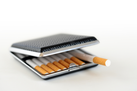the case selected: black and silver cigarette case with tobacco filter cigarettes, background fades to white, copy space, selected focus, very narrow depth of field