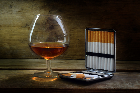 the case selected: Alcohol and tobacco, glass with cognac or brandy and a case with filter cigarettes on warm rustic wood, concept for enjoyment or addiction, selected focus, narrow depth of field