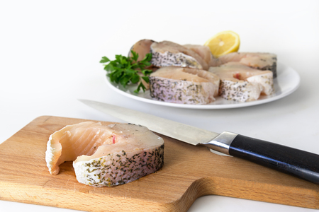 preparing northern pike steaks, fresh raw fish piece and knife on a cutting board, finished steaks on a plate blurry in the bright background, selected focus, narrow depth of field