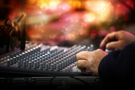 Working sound control panel or mixing console in front of the stage at a music festival concert, selected focus, narrow depth of field, blurry background bokeh