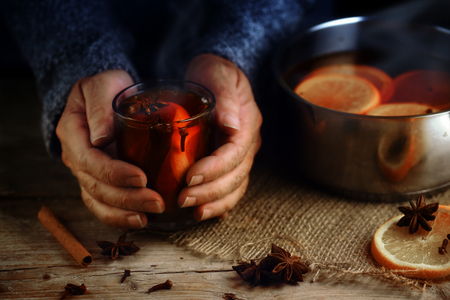 Older female hands holding a glass mug with hot mulled wine next to the steaming cooking pot,  Christmas ingredients, orange slices, cinnamon sticks, star anise and cloves, a warming home scene on a rustic wooden table, selected focus, narrow depth of fie