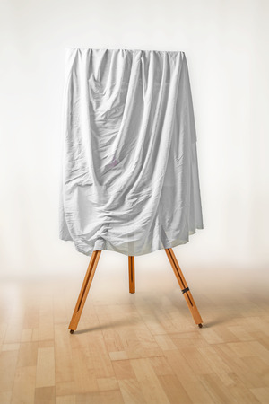 covered painting on an easel, white cloth over the picture, wooden floor and light background, art concept for an exhibition opening day or a presentation ceremony, soft fokus, copy space