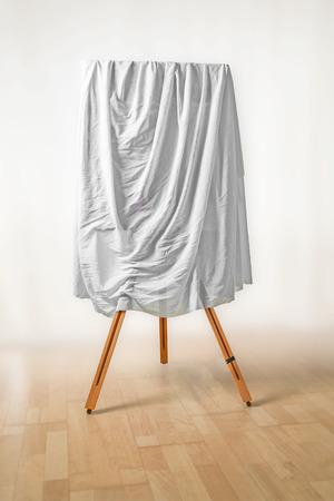 dipinto coperto su cavalletto, panno bianco sopra l'immagine, pavimento in legno e sfondo chiaro, concetto di arte per un giorno di apertura di una mostra o una cerimonia di presentazione, soft fokus, copia spazio