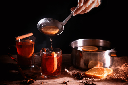 pouring hot mulled wine from in a pot and in glass mugs, Christmas spices like orange slices, cloves, star anise and cinnamon on a rustic wooden table against a dark background, selected soft focus, narrow depth of field Stock Photo