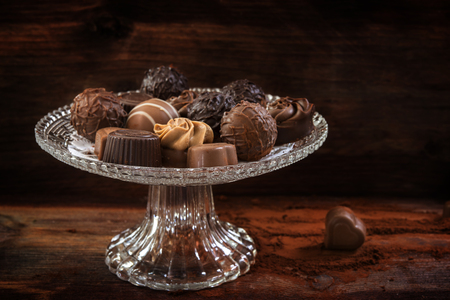 chocolate, assortment of pralines on an elegant glass étagère against a brown wooden background, close up, selected focus, very narrow depth of field