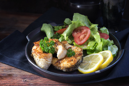 fried northern pike steaks with lemon, lettuce salad and tomatoes on a black plate, healthy low carb meal on a dark rustic wooden background, selected focus, narrow depth of field