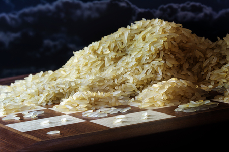 chessboard with growing heaps of rice grains, legend about the exponential function and the limits to growth, dark sky,  selected focus, narrow depth of field
