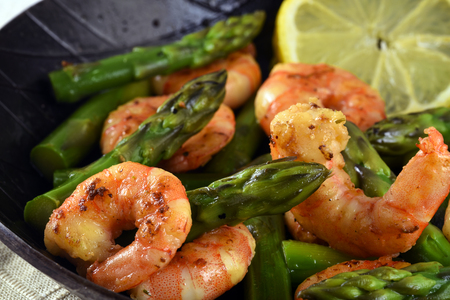fried prawns or shrimps with  green asparagus peaks and a lemon slice in a black iron pan, close up, selected focus, narrow depth of field Stock Photo