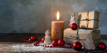 two gift boxes and a burning candle decorated with red christmas baubles and small wooden toy trees in some snow on rustic wood, vintage background with large copy space, panorama format, selected focus, narrow depth of field