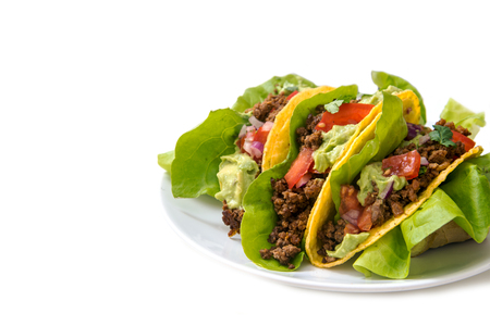 mexican tacos, crunchy corn shells stuffed with fried ground beef, tomato salsa and guacamole on a white background with copy space, selected focus, narrow depth of field
