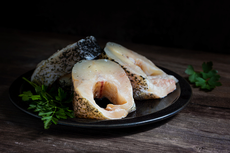 raw northern pike steaks, fresh fish cleaned and prepared for cooking, grilling or frying on a dark rustic wood, copy space, selected focus, very narrow depth of field