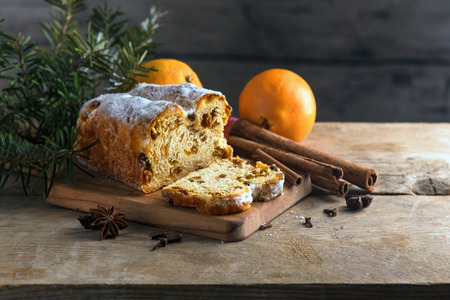 Christmas cake, in germany christstollen with fir branches, oranges, cinnamon and anise stars on a rustic table, wooden vintage background with copy space, selected focus, very narrow depth of field