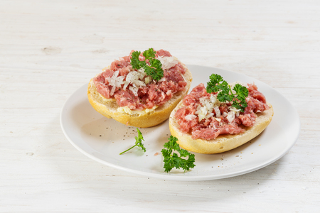 minced pork sausage, german mettwurst with onions and parsley on a bun, white plate on a white wooden table with copy space, selected focus Stock Photo