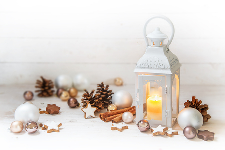 Christmas lantern with burning candle light and decoration like baubles, pine cones and cinnamon star cookies on rustic white wood with copy space, selected focus, narrow depth of field