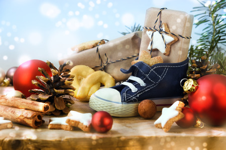 St. Nicholas Day, Childrens shoe with sweets, gifts and christmas ornaments on rustic wood, light blue snowy background, in Germany called Nikolaus, selected soft focus
