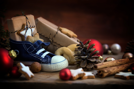 Childrens shoe with sweets and gifts for St. Nicholas Day on December 6th at Christmas time on rustic wood, traditional custom in Germany called Nikolaus, selected focus, narrow depth of field