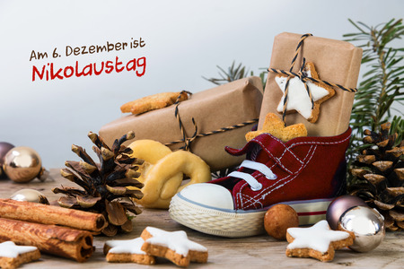 Childrens shoe with sweets, gifts and christmas ornaments on rustic wood, german text Am 6. Dezember ist Nikolaustag, meaning  St. Nicholas Day December 6th, selected focus, narrow depth of field