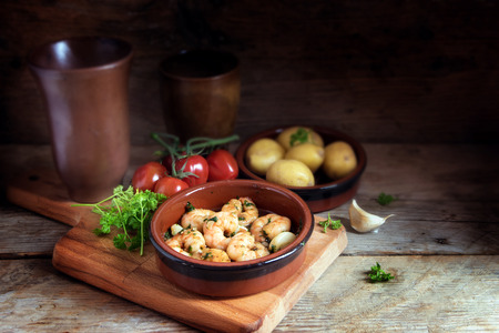 Tapas bowl with shrimps or prawns in garlic olive oil, potatoes, tomatoes and herbs on a rustic wooden table, spanish appetizer, dark background with cop space, selected focus, narrow depth of field