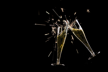 two champagne flutes, toast with splash and sparklers against a black background, new year party concept, copy space