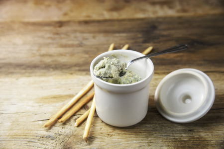 potted blue stilton cheese on a spoon and in a ceramic jar, some nibbles sticks on a rustic wooden table, copy space, selected focus, narrow depth of field