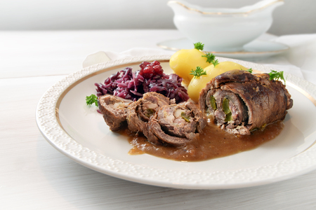 beef roulade with red cabbage and potatoes, german meat roll stuffed with cucumbers, bacon and onions on an elegant white gold rim plate on a light wooden table, copy space, selected focus, narrow depth of field