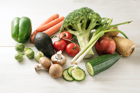 various vegetables such as broccoli, carrots, peppers, parsnip roots, mushrooms, tomatoes, green onions, avocado, brussels sprouts on a white wooden background, concept of healthy food and slimming low carb diet Banco de Imagens