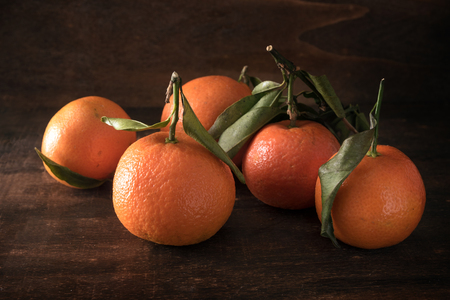 fresh clementine fruits with leaves on a dark rustic wooden background, selected focus, narrow depth of field