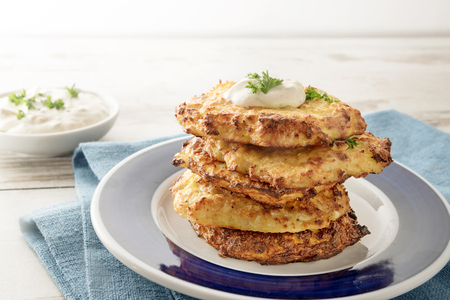 Pile of golden crisp vegetables rosti from cauliflower and parmesan cheese with a creamy dip and parsley garnish on a blue napkin