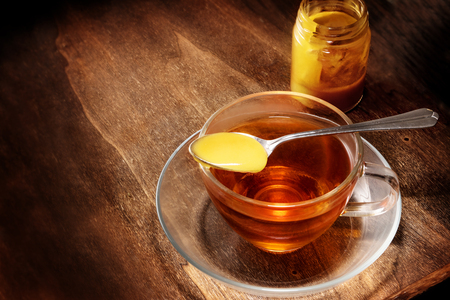 black tea in a glass cup and a spoon with honey on rustic dark wood, healthy hot drink with cold and flu, copy space, selected focus