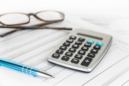 calculator, pen and glasses on a printed financial report with number tables, business concept for finance, economy and taxes, selected focus, narrow depth of field
