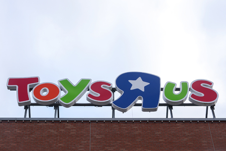 Luebeck, Germany - February 1, 2018: Toys r us brand logo on a building against the cloudy sky. Toys are us is an American toy and juvenile products retailer and operates as a chain with global stores Editorial