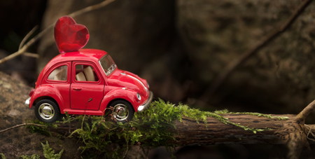 Rieps, Germany - February 1, 2018: red miniature car carries on a tree trunk in a rocky landscape