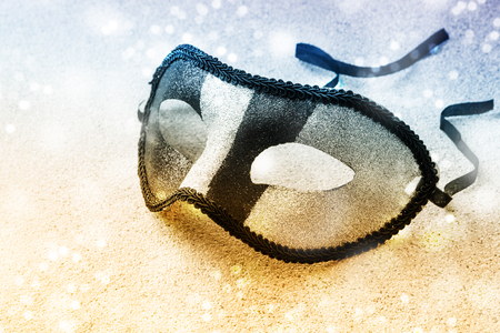 carnival mask in sparkling silver and black stripes  on a snowy gold blue background with copy space, selected focus, narrow depth of field Stok Fotoğraf