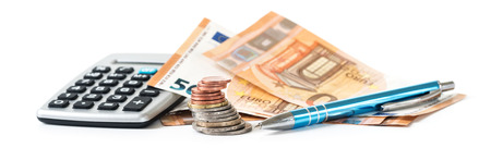 financial planning with coins and euro banknotes, a calculator and a pen isolated on a white background, panoramic banner format, selected focus, narrow depth of field Archivio Fotografico
